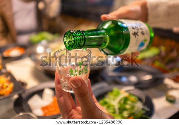 Restaurant in SEOUL,SOUTH KOREA-JANUARY 2016; Pouring Soju in glass with food blur background