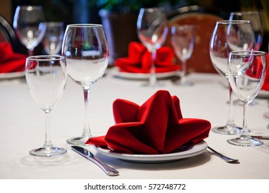Restaurant served table wine glasses and plate. White tablecloth, red napkins, crockery and cutlery.