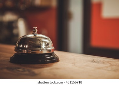 Restaurant service bell on the table vintage with bokeh, evening light background.Business concept Serve today hotel, kitchen or bar visit.