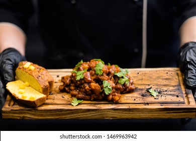 Restaurant service. Cropped shot of chef holding wooden board with cornbread and Boston baked beans decorated with green parsley.