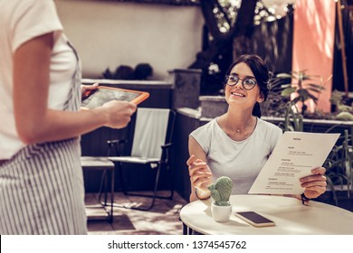 Restaurant service. Joyful dark haired woman smiling to the waitress while making an order