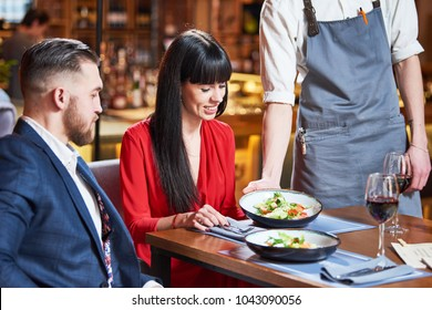 Restaurant service. young couple and waiter with salad plates