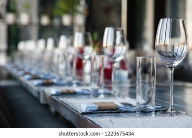 Restaurant serving, glass wine and water glasses, forks and knives on textile napkins stand in a row on a gray wooden table. Concept banquet, birthday, conference, group lunch