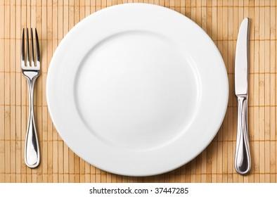 Restaurant serving (metal fork, knife and ceramic white plate)