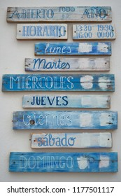 Restaurant sign in Spain saying 'Abierto todo el ano' (open all year), 'Horario' (opening times) and all the weekdays in Spanish, painted on wooden panels