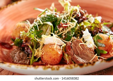 Restaurant Starter Menu of Duck Breast Salad with Crispy Potato Balls on Rustic Style Hay Background Close Up. Macro Photo of Meat Salat with Whole Potatoes, Soft Cheese, Lettuce and Arugula Leaves