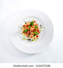 Restaurant Starter Menu with Raw Salted Salmon Slices, Tomato and Cucumber Isolated on White Background. Diced Red Fish or Trout with Vegetables, Herbs and Spices on Elegant Flat Plate Top View