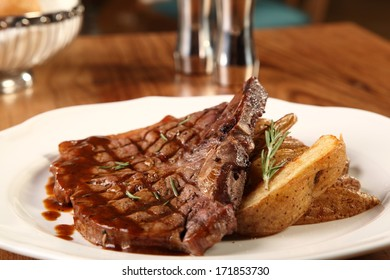 Restaurant table with beefsteak and fried potatoes served