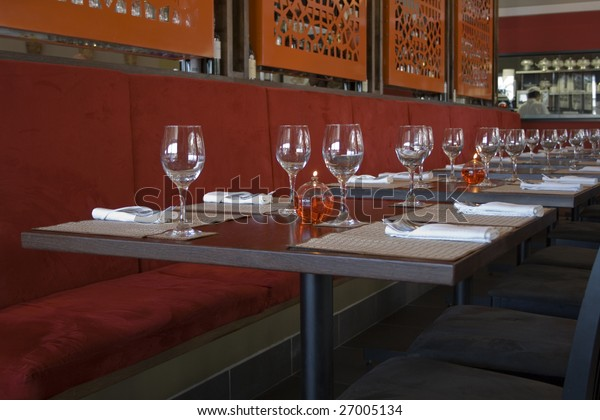 Restaurant table with candle wine glasses and cutlery, with kitchen background.