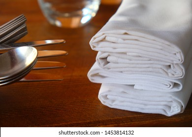A restaurant table on the left are knives, forks and spoons stacked ontop of each other on the right four white linen napkins, wooden table, warm colours.