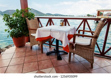 Restaurant table on the outdoor terrace near the water.