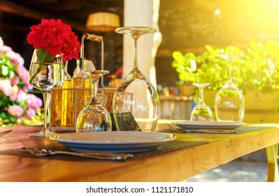 Restaurant table set for dining outside on the terrace in Mediterranean style, with cutlery, wine glasses and condiments