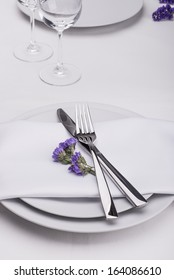Restaurant table set with purple flowers