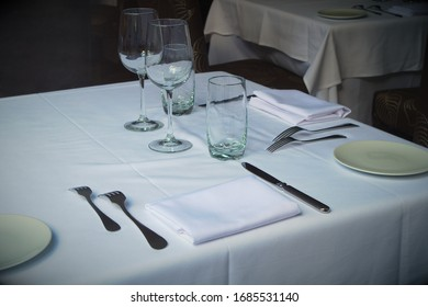 restaurant table setting white tablecloth napkins and glass