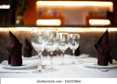 Restaurant table with two menu sets and a bar in the background