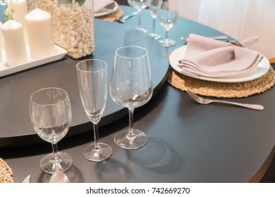 Restaurant table with wine glasses and napkins.