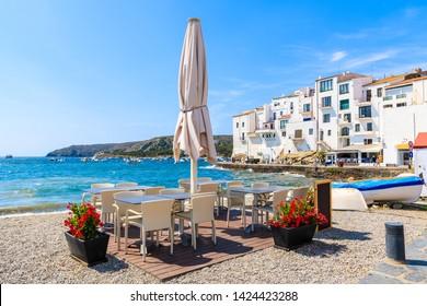 Restaurant tables along sea in Cadaques village, Costa Brava, Spain