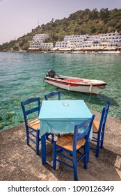 Restaurant tables by the sea in the scenic village of Loutro  in Crete, Greece