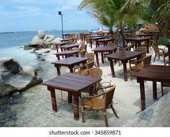 Restaurant tables and chairs in the sand ready for seaside dining on the beach in Aruba, Caribbean