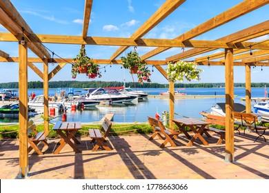 Mesas de restaurante en terraza con flores y vistas a los veleros en el lago Beldany en el puerto de Piaski en el verano soleado, distrito de Mazury Lake, Polonia