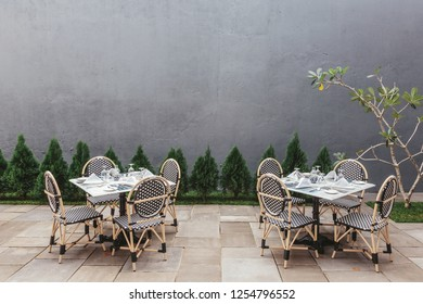 Restaurant tables outdoor with little Christmas trees and grey wall on background