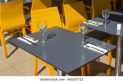 restaurant tables with silverware and glasses ready for a lunch or dinner