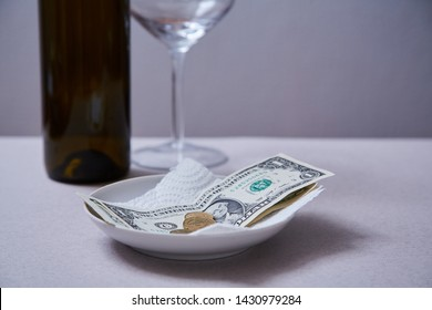 Restaurant tips or gratuity. Banknotes and coins on a plate