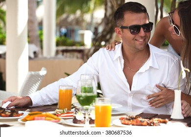 Restaurant tourists couple eating at outdoor restaurant. Summer travel people eating healthy food together at lunch during holidays in Caribbean paradise.