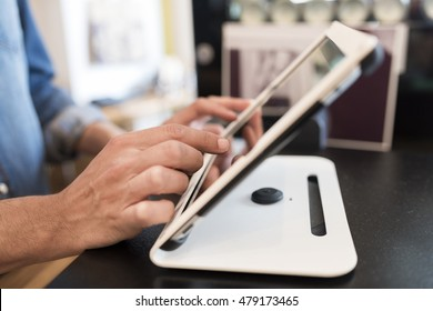 In a restaurant the waiter prepares the bill on computer POS tablet pc. The waiter takes the order on digital tablet