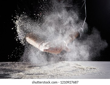 Restaurant worker in black suit and latex gloves wiping white powdery flour off hands onto rectangular