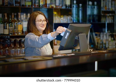 A restaurant worker registrating new order by cash-register. The concept of maintenance and service.