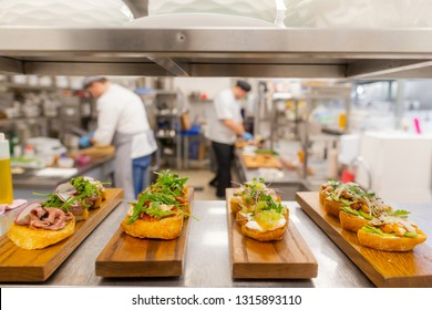 Restaurants kitchen. Italian bruschetta. Toast bread. Healthy premium food. Served meal. Preparing food. Meat and green.