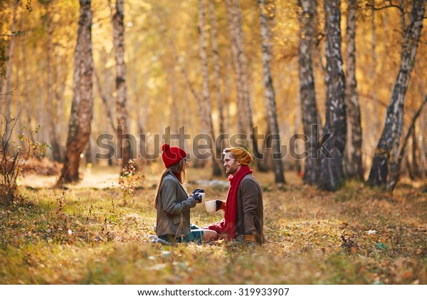 Restful couple drinking tea at leisure in park