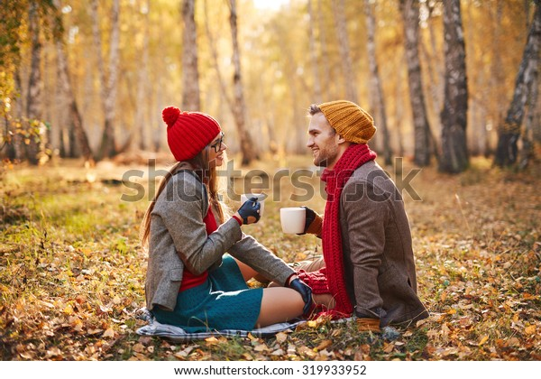 Restful couple in warm clothes enjoying outdoor tea in park