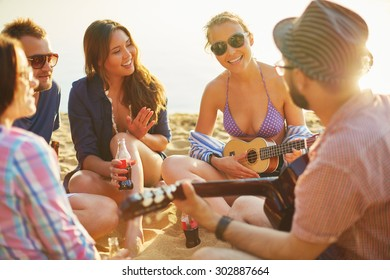 Restful friends with drinks and guitar spending leisure on sandy beach