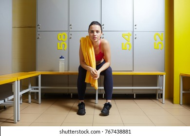 Restful girl with towel sitting in changing room on bench after workout