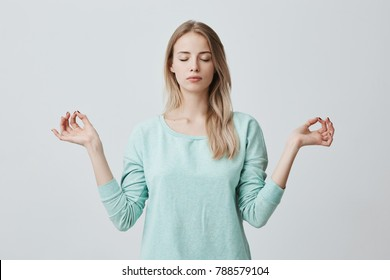 Restful peaceful blonde female feels relaxed, stands in lotus pose, tries to concentrate or to be focused, closes eyes, enjoys silence, tries to find balance. Calm atmosphere and meditation
