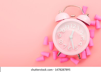 Restful sleeping, wear ear plugs and how to hearthe alarm clock without missing sleep due to noise concept theme with earplugs and vintage clock isolated on pink background with copy space