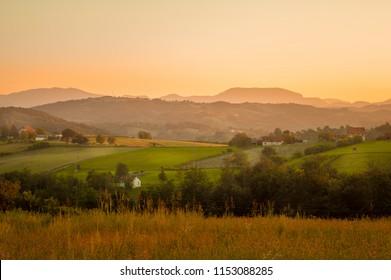 Restful village landscape. Summer evening in western Serbian village. Fields and forest with mountains in background. Near town of Valjevo, Serbia, Europe.