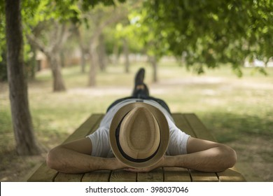 Restful young man wearing a straw hat laying down on a wooden table in the middle of the forest at a park