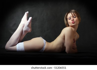 Resting flirty girl with long slim legs in white nylons. Vintage style low key photography. Great for calendar