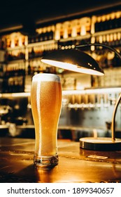 Resting. Full glass of light lager beer with drops on the side, wooden table in warm light of bar. Alcohol, entertainment, traditional drinks, Oktoberfest atmosphere concept. Modern bar, vertical crop