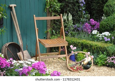 Resting in the garden, Wooden seat and gardening equipment in perfect English cottage garden
