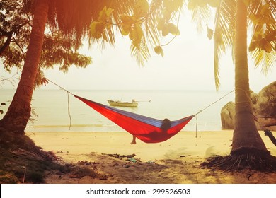 Resting in Hammock by the sea  on a sand beach at sunset time