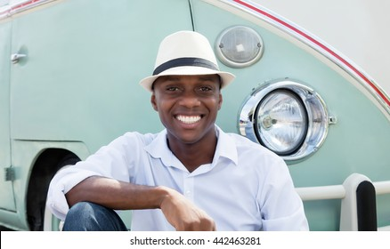 Resting man from Cuba with straw hat and old car