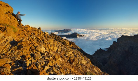 Resting man showing to a landscape above the crater Caldera de Taburiente, Island of La Palma, Canary Islands, Spain