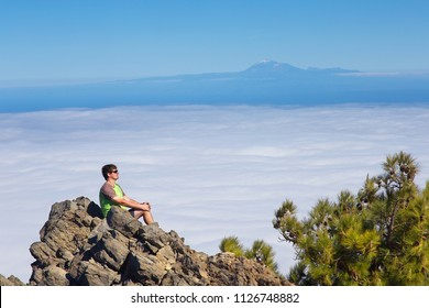 Resting man watching a landscape with a mountain of Pico de la Teide on background, Island of La Palma, Canary Islands, Spain