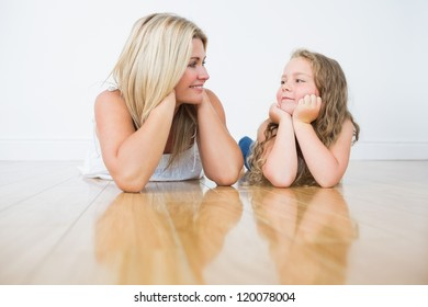 Resting mother and daughter on the floor while they looking at each other