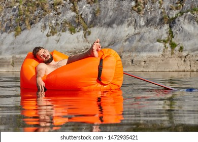 Resting in nature, businessman fell asleep in an inflatable lounger drifting along the river, his hand with a mobile phone clasped in it, is in water, and the phone is wet.