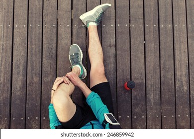 resting sportsman's legs sitting on the wooden floor with red sport plastic bottle, view from the top